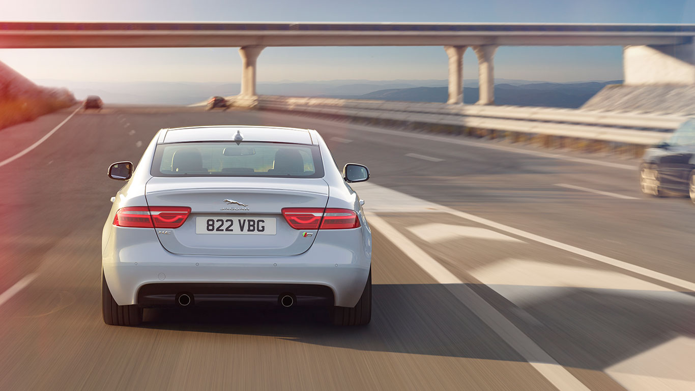 White Jaguar XE Back View on The Road