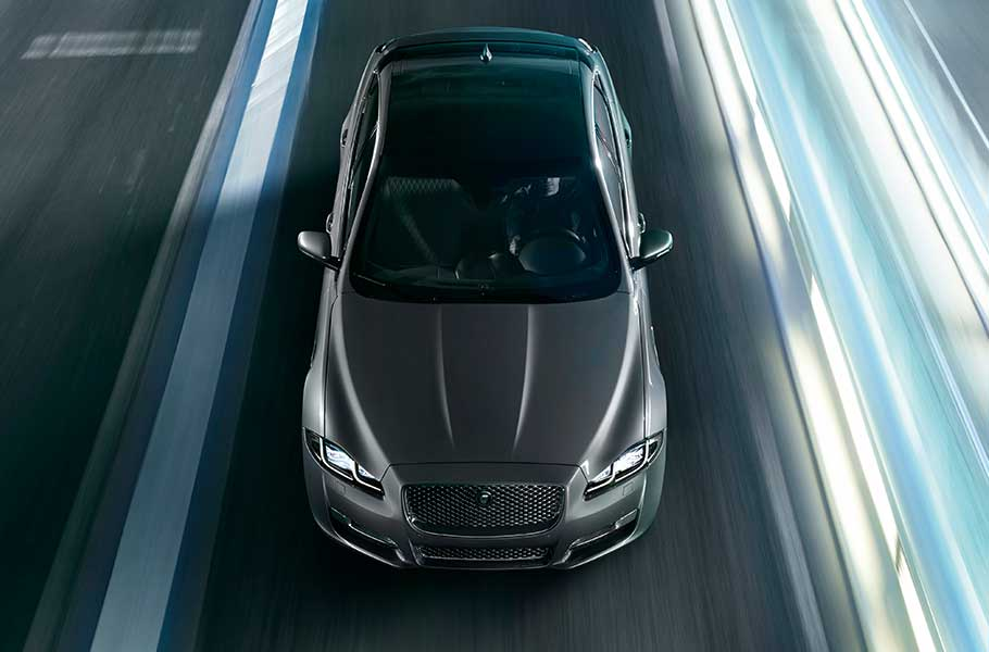 Grey Jaguar XJ driving on bridge road