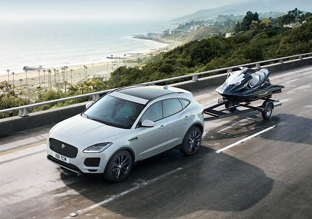 White E PACE driving whilst towing a jet ski on road next to beach