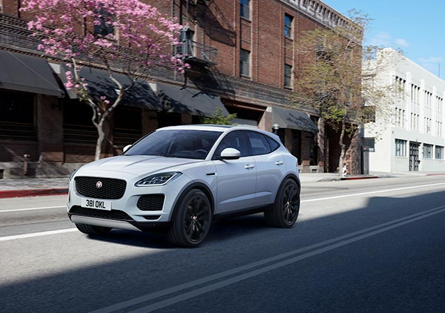 White Jaguar E PACE driving on street road