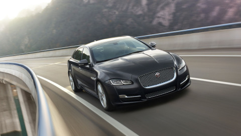 Jaguar XJ Dark Blue Driving on Road