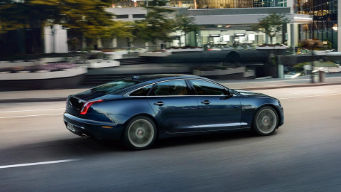 Jaguar XJ in blue driving on road