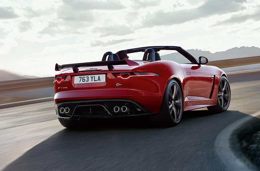 Jaguar F-TYPE SVR Convertible Sports Car takes a corner, with mountains in the distance