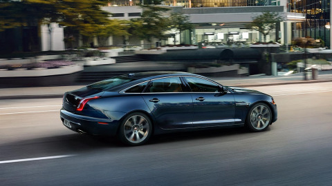 Jaguar XJ in dark blue driving on road