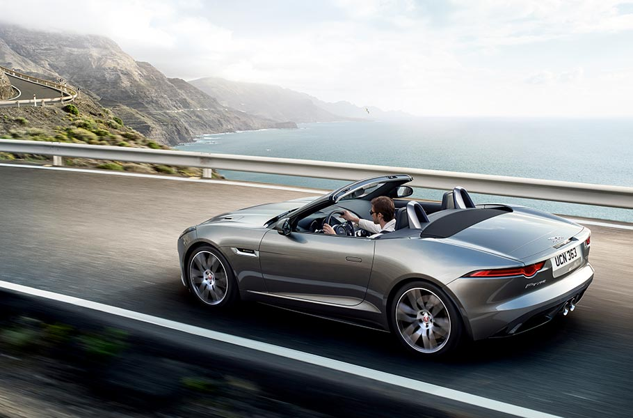 Jaguar F-TYPE R-DYNAMIC Converible Sports Car drives along a cliffside road, a mountainous coastline stretches off into the distance behind it