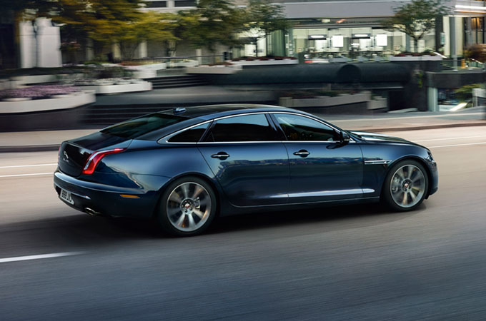 Blue Jaguar XJ Driving Along Road.