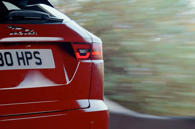 Rear of Jaguar E-PACE driving along road.