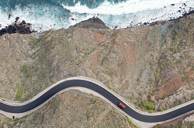 Aerial view of Jagauar E-Pace driving along winding road.