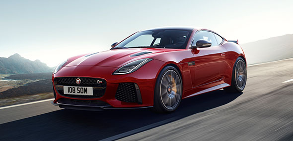 Red Jaguar F TYPE Coupe driving on road