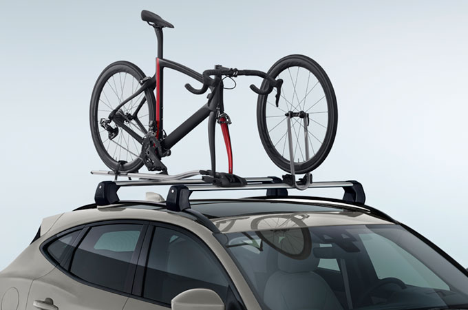 Jaguar E-Pace with bicycle mounted on roof cycle carrier.