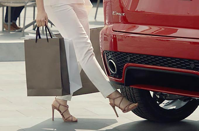 Woman holding shopping bags using her foot to activate the powered gesture tailgate.