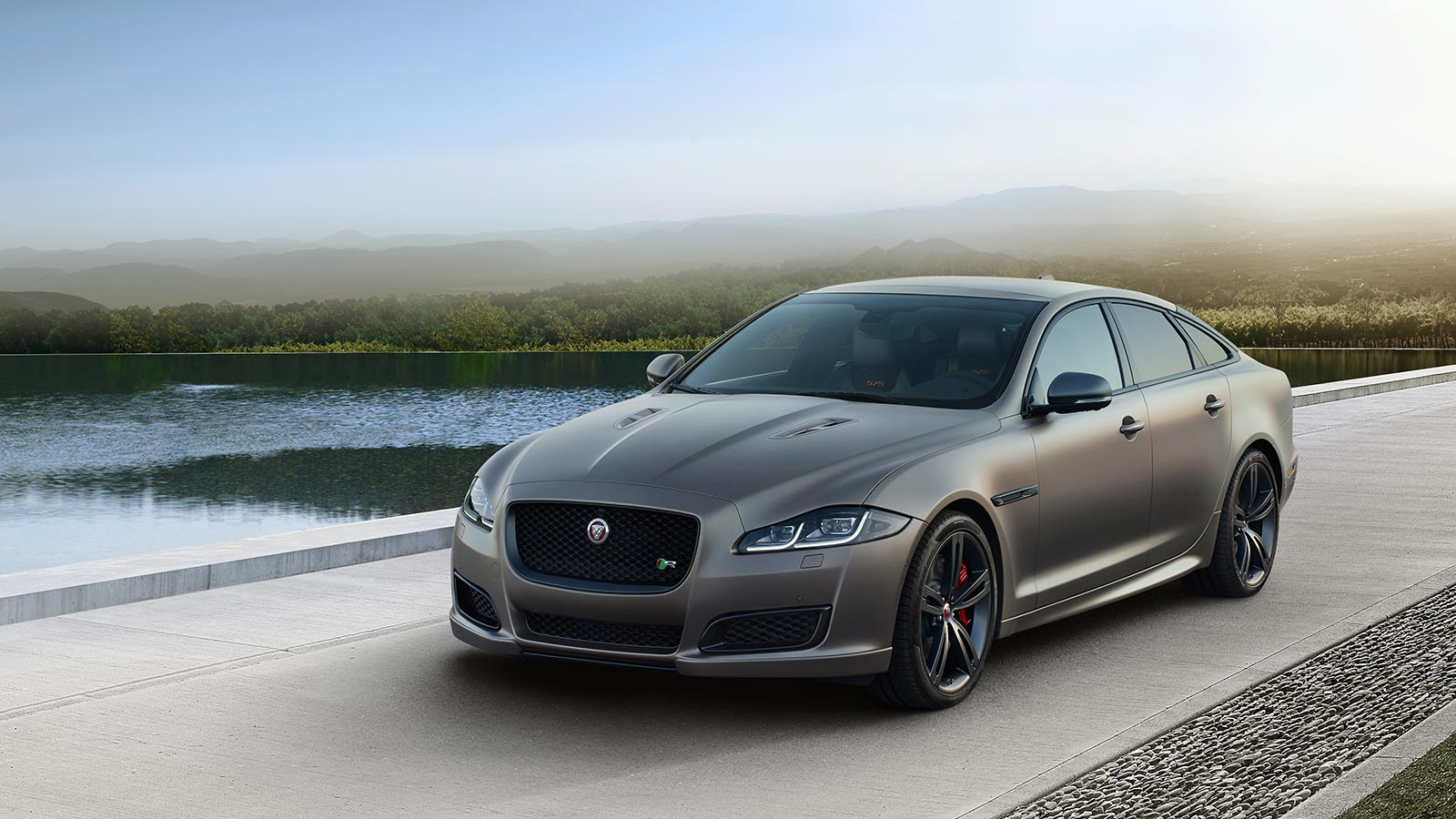 Jaguar XJR575 Driving on Road Near Water.