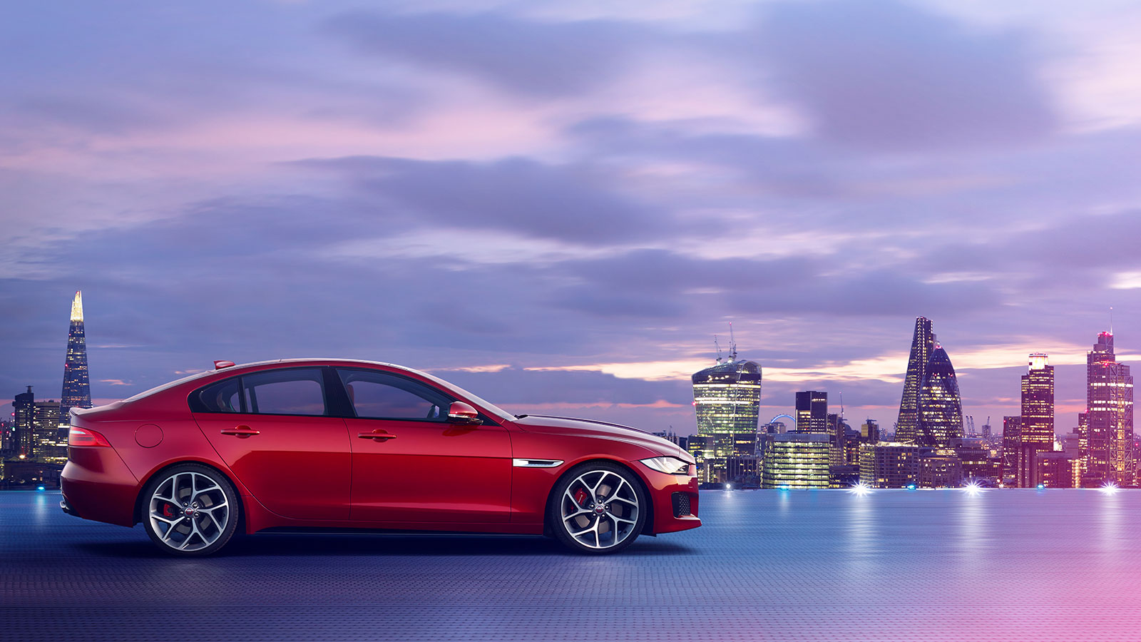 Night view of Jaguar XE, with London city skyline.