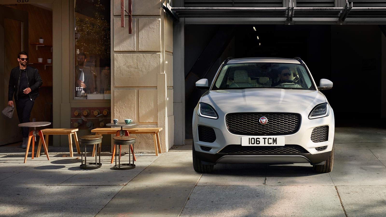 E-PACE S IN BORASCO GREY WITH OPTIONAL FEATURES FITTED PARKED NEAR A CAFÈ.