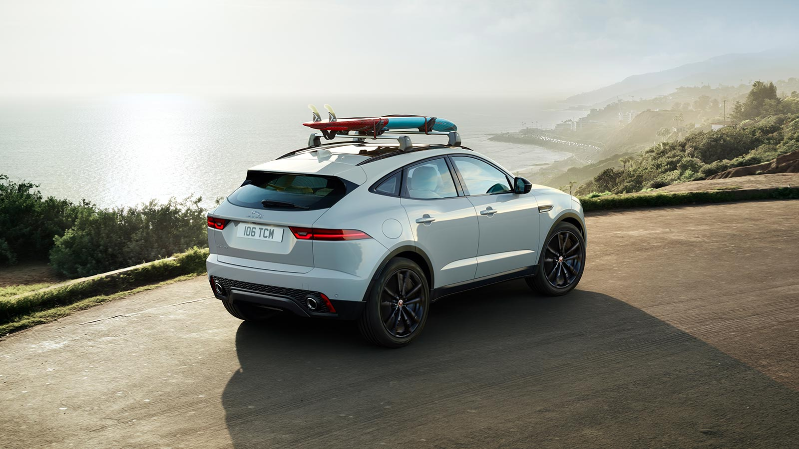 E-PACE S IN BORASCO GREY WITH OPTIONAL FEATURES FITTED DRIVING ALONG A SEASIDE ROAD WITH A SURF BOARD ON THE ROOF.