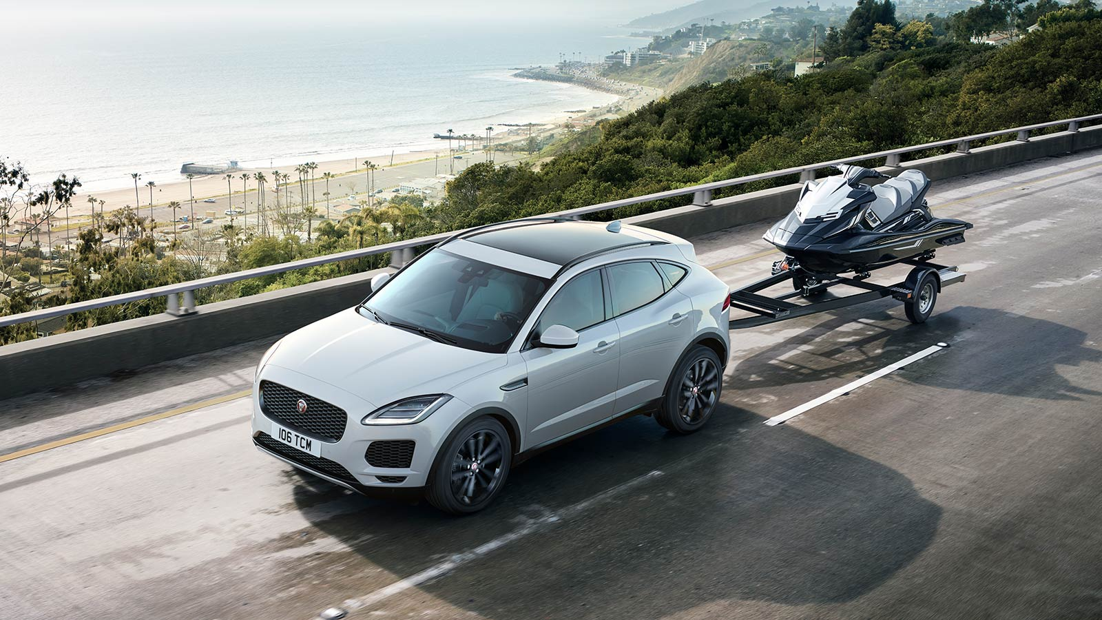 E -PACE S IN BORASCO GREY WITH OPTIONAL FEATURES FITTED TOWING A JETSKI ALONG A SEASIDE ROAD.