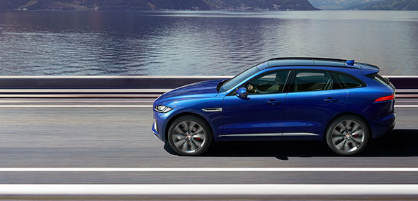 Blue Jaguar F-PACE driving on road