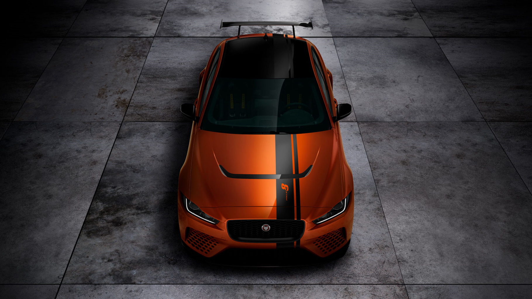 Jaguar XE SV Project 8 in orange with a black strip on grey slabs