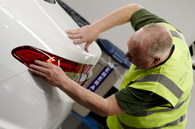 Mechanic examining the brake light of a white Jaguar vehicle.