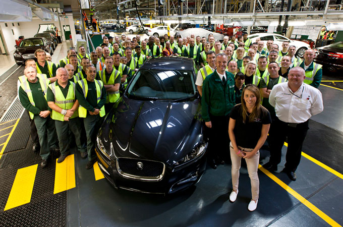 Jaguar Land Rover workers with a Jaguar XJ in navy inside factory line.