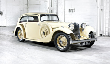 Jaguar 1935 S.S.I Airline Saloon in yellow inside a white warehouse.