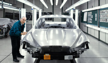 A worker inspecting a chassis of a silver Jaguar vehicle.