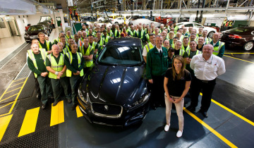 Workers with a Jaguar XJ in navy inside a factory line.