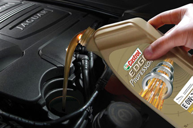 An individual pouring Castrol EDGE Professional into their Jaguar engine.