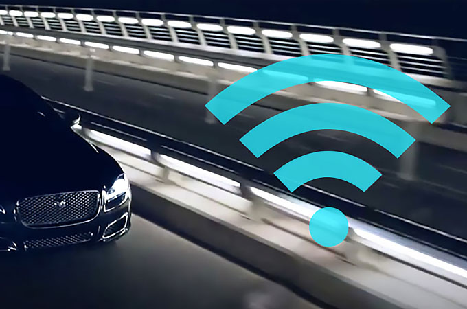 Wifi Logo overlaying a Jaguar driving at night