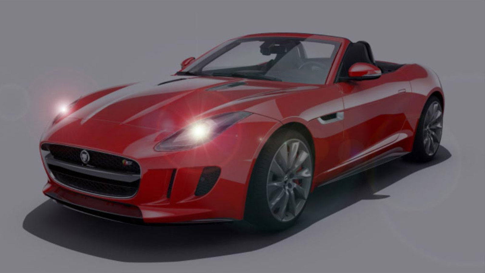 A Red Jaguar With The Headlights Turned On