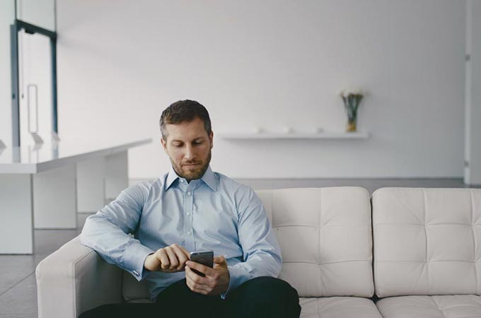 Man sat on sofa using his phone
