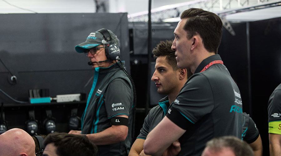 A group of Jaguar Racing team members, which includes driver Mitch Evans and Director James Barclay, look at information in the pits.