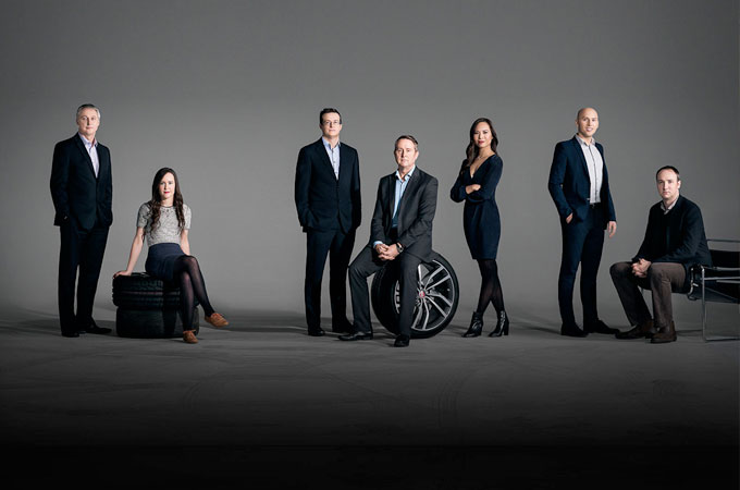 Jaguar experts, dubbed the 'magnificent seven' pose on tyres and chairs.