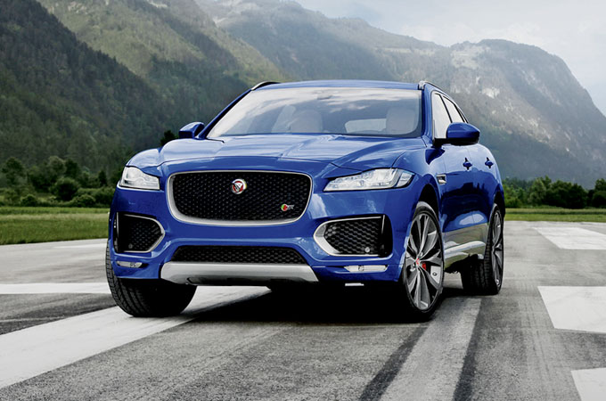 The Jaguar F-PACE parked on a strip of tarmac, in front of hills.
