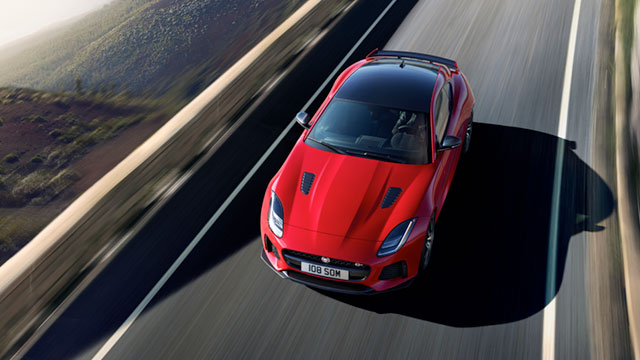 Red Jaguar F-Type Driving on Road