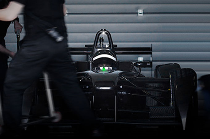 A dimly-lit front view of the whole I-TYPE 2, with engineers working around it.