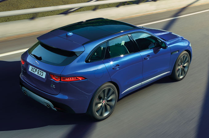 Rear-side view of Jaguar F-Pace driving on-road.