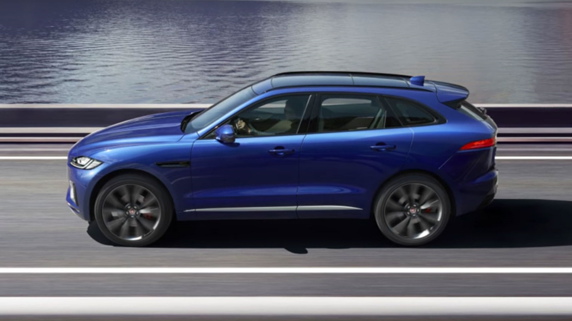 A jaguar F-Pace driving along a road by the sea.