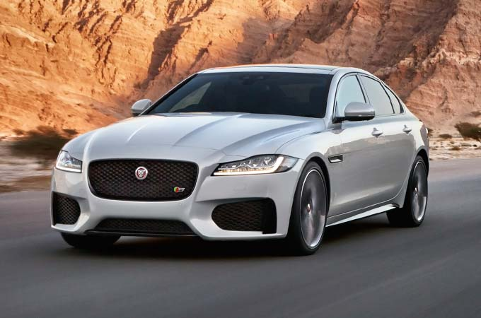 Jaguar XF driving along a road in front of sandstone cliffs.