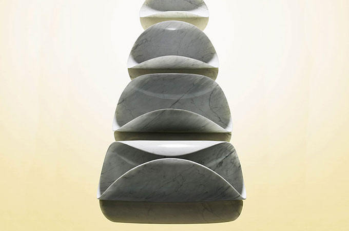 A row of marble chips getting progressively less curled into the centre on a yellow background.