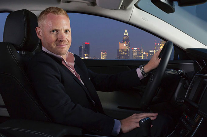 Creative Director, Exterior Design, Adam Hatton, sitting inside a vehicle with a city at night behind.