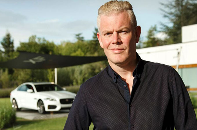 Production Studio Director and SVO Projects, Wayne Burgess, with a Jaguar XF in white behind.