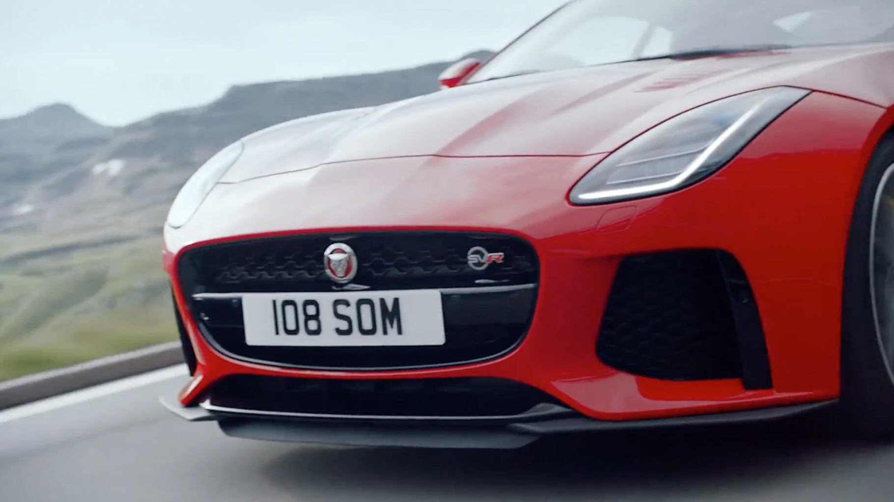 a closeup of the front of a jaguar f-type in red, whild driving.