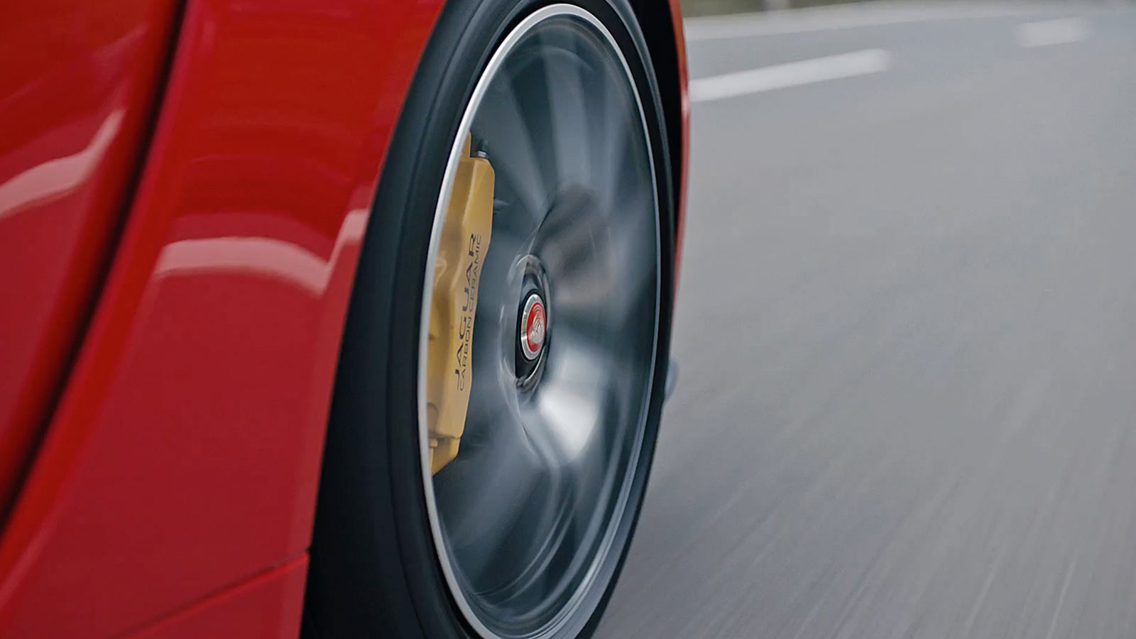 A close up of a jaguar f-type wheel while driving.