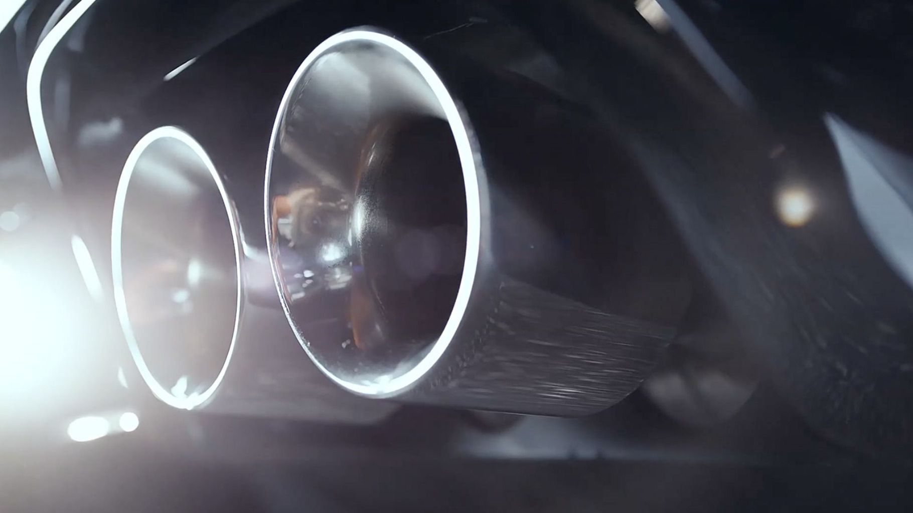 Close up of a jaguar f-type dual exhaust pipes.