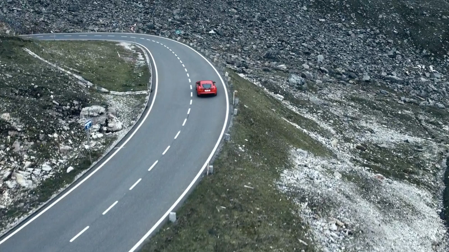 A jaguar f-type driving on a road through mountainous terrain.