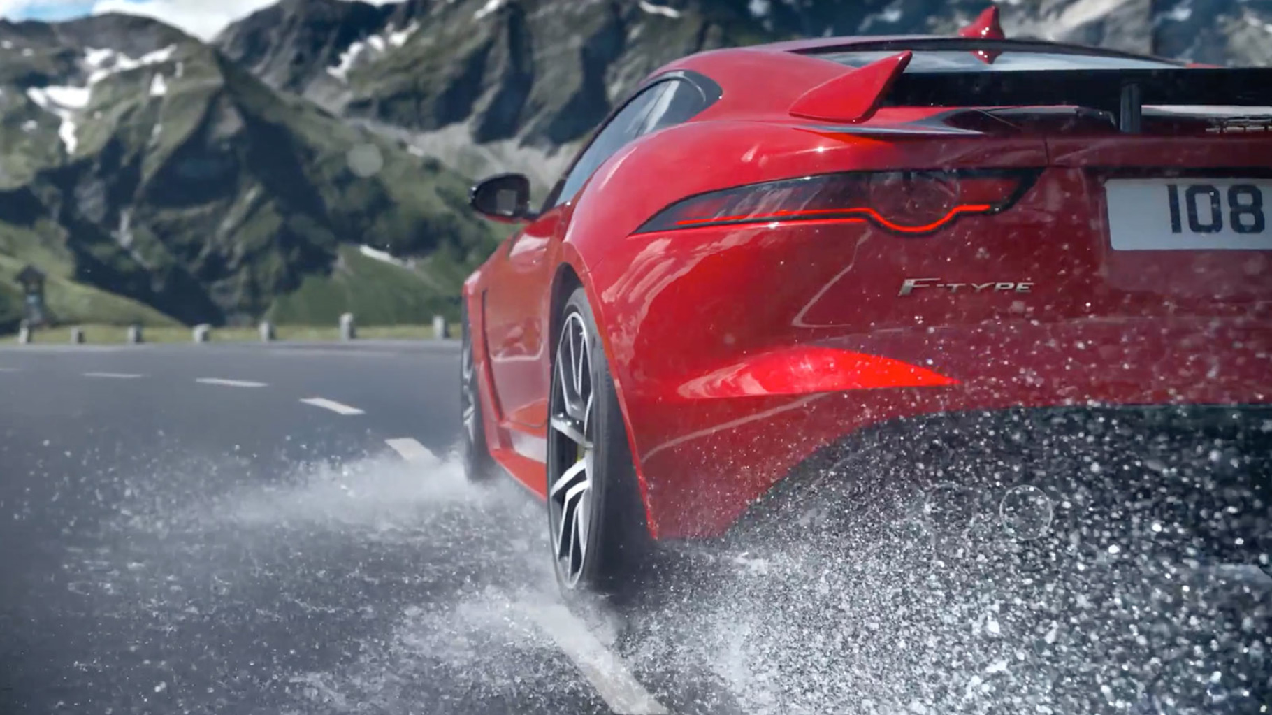A jaguar f-type driving on a wet road kicking up water as it speeds.