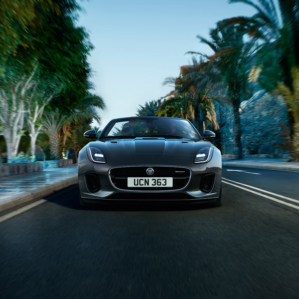 The front of a jaguar f-type coupe driving down a road with palm trees on either side.
