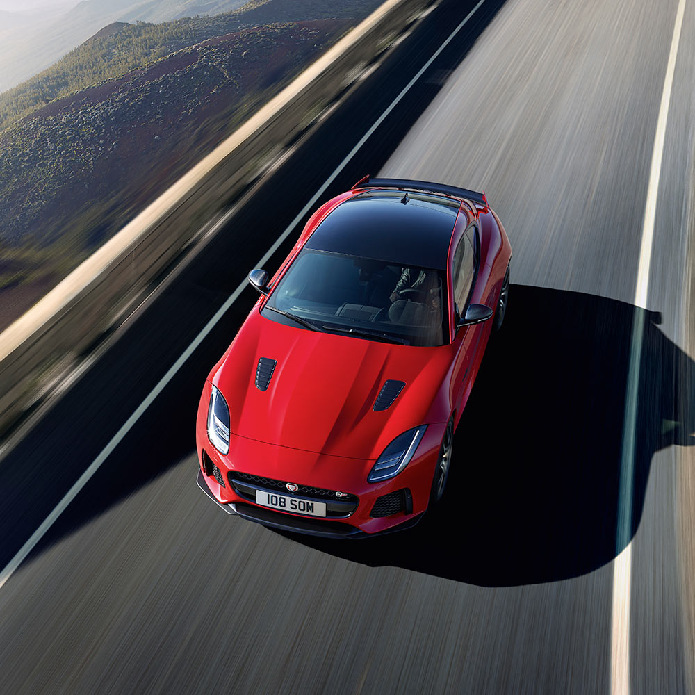 An aerial view of a jaguar f-type coupe driving on a bridge.