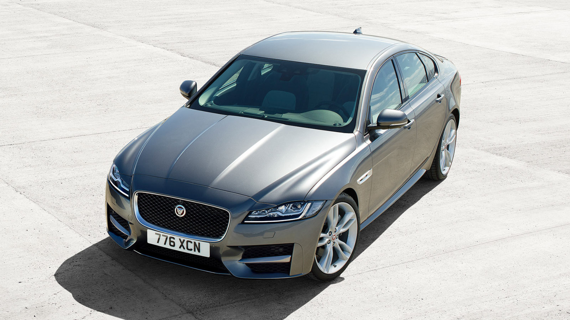 A grey Jaguar XF Saloon parked in the sun.